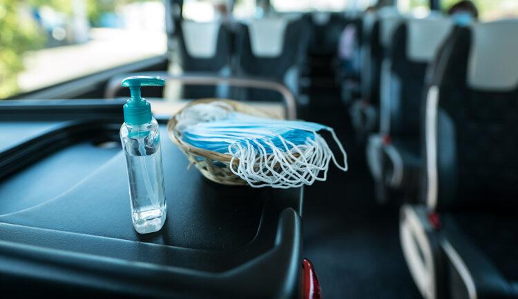 Mascarillas y gel desinfectante en la entrada de un autocar turístico